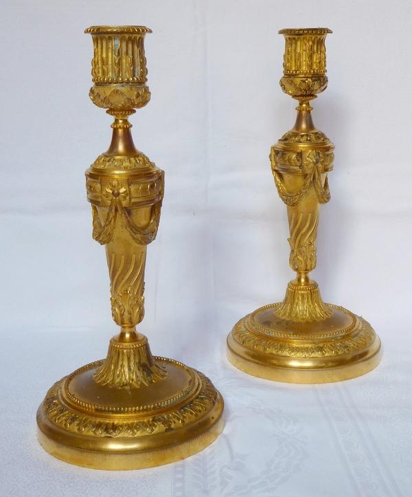 Paire de bougeoirs de style Louis XVI en bronze ciselé et doré