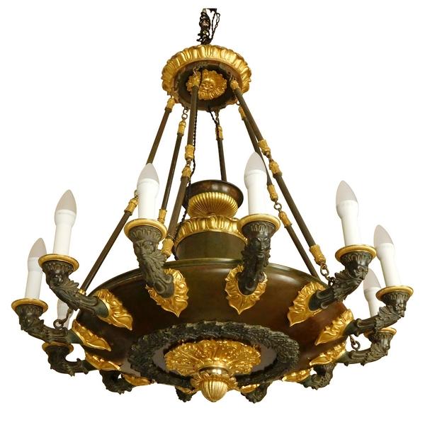 Grand lustre Empire à 12 feux aux barbus en bronze doré et patiné, époque début XIXe